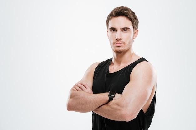 Изображение красивого молодого человека, одетого в черную футболку, стоящего над белой стеной со скрещенными руками