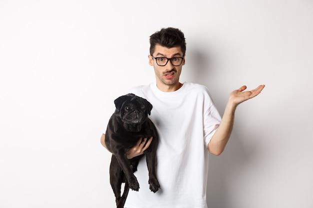 Изображение красивого молодого человека, держащего черного мопса и выглядящего смущенным. парень пожимает плечами и нерешительно смотрит в камеру, держит собаку на руке, белый фон