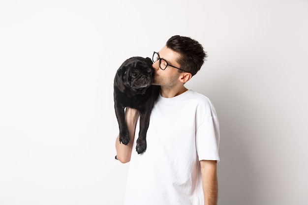 Изображение красивого молодого человека, целующего своего симпатичного черного мопса, держащего собаку на плече, стоящего на белом фоне