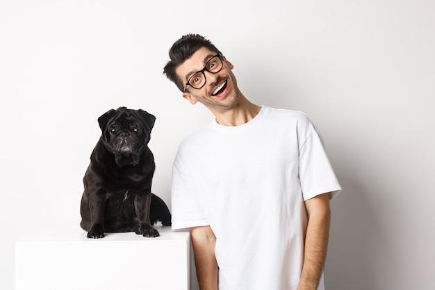 かわいい黒いパグの近くに立って笑っているハンサムな若い男の画像。彼のペットと一緒に時間を過ごし、カメラの幸せな白い背景を見つめている犬の飼い主