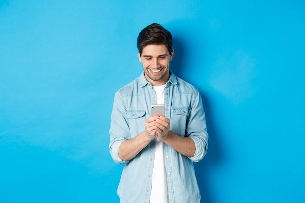 携帯電話を使用して、電話でテキストメッセージを送信し、青い背景の上に立って満足そうに見えるハンサムな若い男の画像。