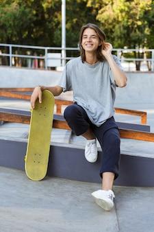 ハンサムな若いスケーターの男の画像は、スケートボードで公園に座っています。