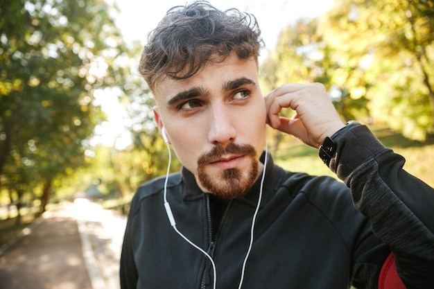 이어폰으로 공원 듣는 음악에 야외에서 잘 생긴 젊은 스포츠 피트 니스 남자 러너의 이미지.