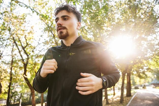 Изображение красивого молодого спортивного бегуна человека фитнеса на открытом воздухе в парке.