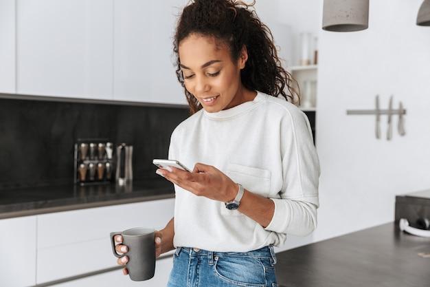 明るいフラットに立っている間、お茶を飲み、携帯電話を保持している幸せなアフリカ系アメリカ人の女の子の画像