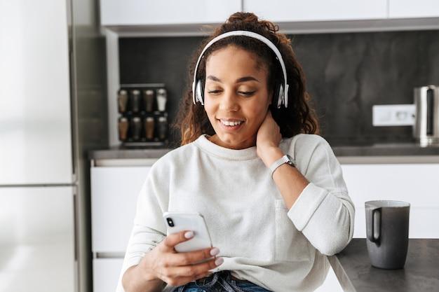 明るいキッチンに座って、スマートフォンを使用してヘッドフォンを身に着けている幸せなアフリカ系アメリカ人の女の子の画像
