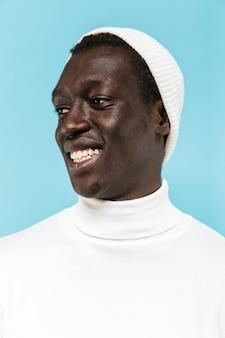 Изображение счастливого афро-американского парня в белой одежде, улыбающегося и смотрящего в сторону