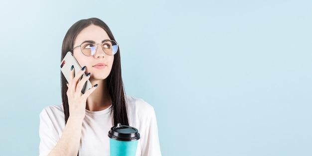 コピースペースで青い壁に隔離されたコーヒーを飲みながら笑顔で友人を呼んで幸せなアメリカ人女性の画像