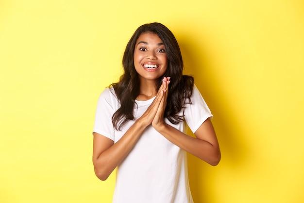 Изображение счастливой и довольной афроамериканской девушки хлопает в ладоши и выглядит взволнованной и благодарит