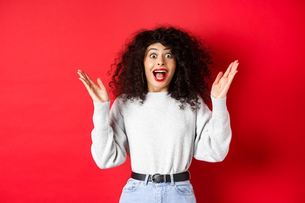 메이크업과 운동복에 행복하고 놀란 곱슬 여자의 이미지는 빨간색 배경에 서있는 좋은 소식에서 손을 올리고 기뻐합니다.