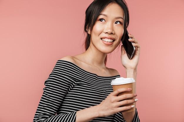 빨간 벽에 격리된 휴대전화로 통화하는 동안 종이컵을 들고 기본적인 옷을 입은 행복한 아시아 여성의 이미지