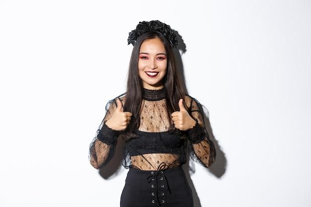 Изображение счастливой азиатской женщины в платье партии хеллоуина показывая большие пальцы руки вверх в одобрении. девушка, одетая как ведьма или вдова, выглядит довольной, нравится или соглашается с чем-то, белый фон.