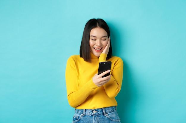 휴대 전화 화면에서 메시지를 읽고 웃 고, 스마트 폰 앱에서 채팅, 파란색 배경 위에 서있는 행복 한 아시아 여자의 이미지.