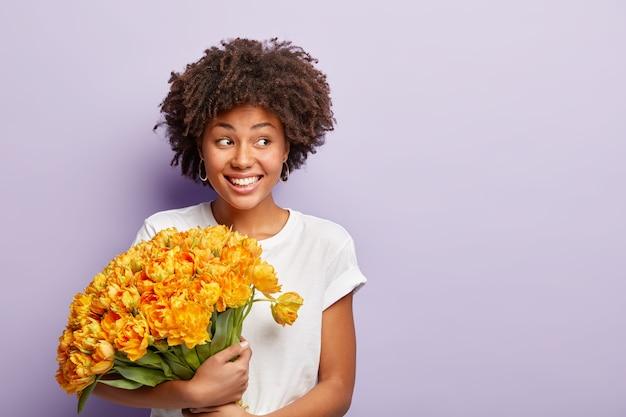 생일 축하 여성의 이미지, 특별한 날을 축하하고, 오렌지 꽃의 큰 꽃다발을 얻고, 캐주얼 티셔츠를 입고, 옆으로 집중하고, 얼굴에 미소를 지으며, 옆으로 보이며, 손님을 만나, 캐주얼 티셔츠를 입습니다.