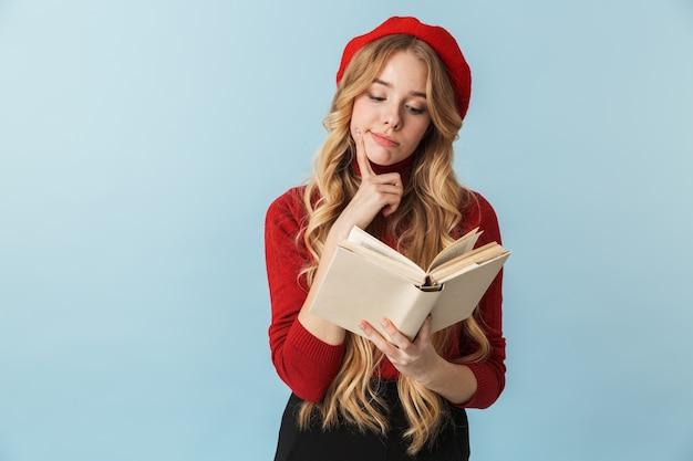 Изображение счастливой белокурой женщины 20-х годов в красном берете, читающей книгу изолированы