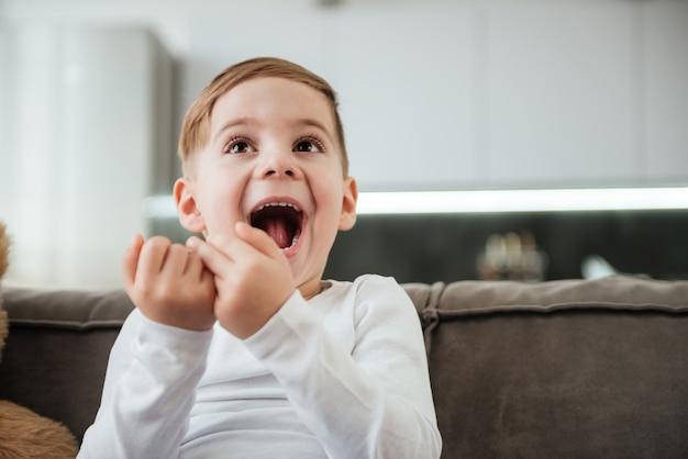 Изображение счастливого мальчика на диване с плюшевым мишкой дома, смотрящего телевизор.