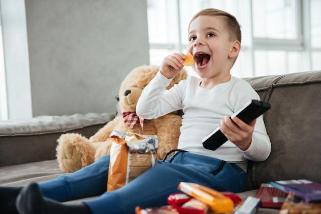 Изображение счастливого мальчика, сидящего на диване с плюшевым мишкой дома и смотрящего телевизор во время еды чипсов. держите пульт дистанционного управления.