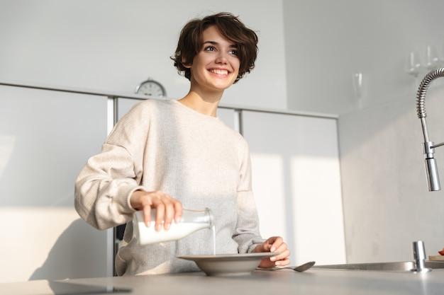 キッチンでテーブルのそばに立って夕食を食べている幸せなブルネットの女性の画像