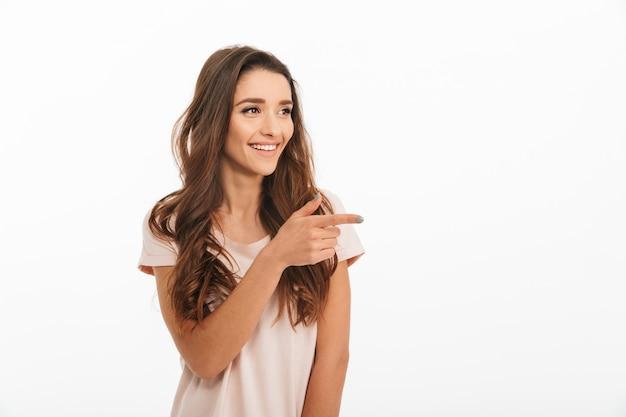 Tシャツを指すと白い壁をよそ見で幸せなブルネットの女性のイメージ