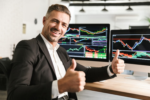 Изображение счастливого бизнесмена 30-х годов в костюме, работающего в офисе на компьютере с графикой и диаграммами на экране