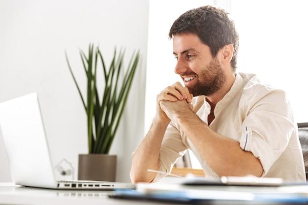 Изображение счастливого бизнесмена 30-х годов в белой рубашке, работающего с ноутбуком и бумажными документами, сидя в современном офисе