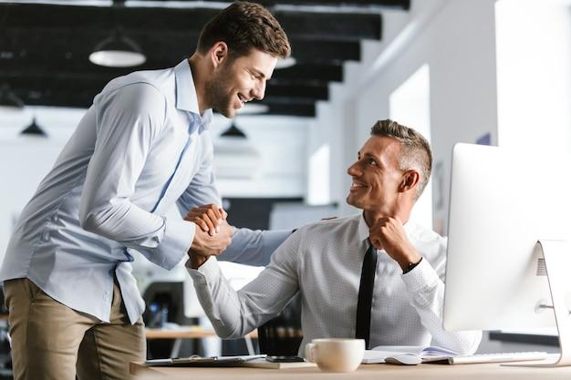 オフィスで働いて、一緒に握手するフォーマルな服を着た30代の幸せなビジネスマンの同僚の画像