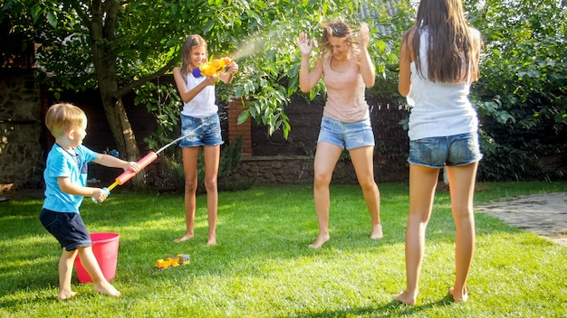 水鉄砲と庭の家で遊んでいる若い母親と幸せな陽気な子供たちの画像。夏に屋外で遊んで楽しんでいる家族