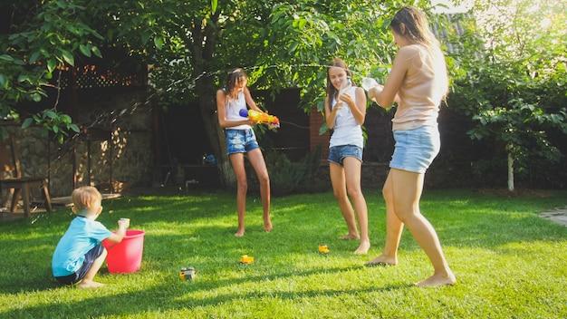裏庭の庭で遊んでいる幸せな陽気な家族の画像。水鉄砲とガーデンホースで水をはねかける人々。