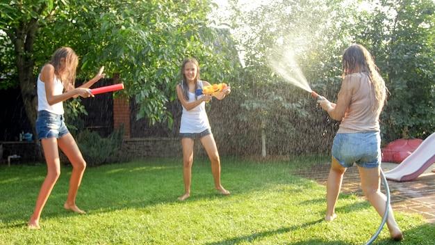Изображение счастливой веселой семьи, играющей в саду на заднем дворе. люди плещут воду из водяных пистолетов и садового шланга.