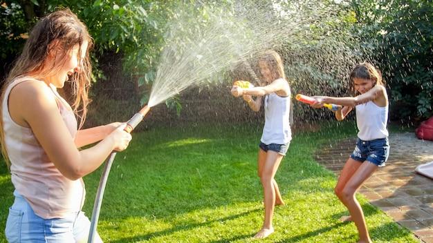 水鉄砲とガーデンホースで家の裏庭の庭で遊んでいる幸せな子供たちの画像。夏に屋外で遊んで楽しんでいる家族