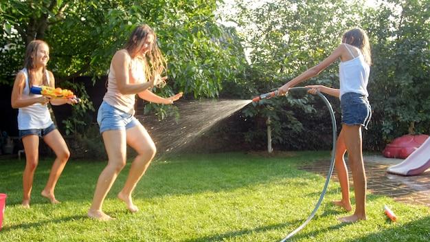 Изображение счастливых детей, играющих в саду заднего двора дома с водяными пушками и садовым шлангом. семья играет и развлекается на открытом воздухе летом