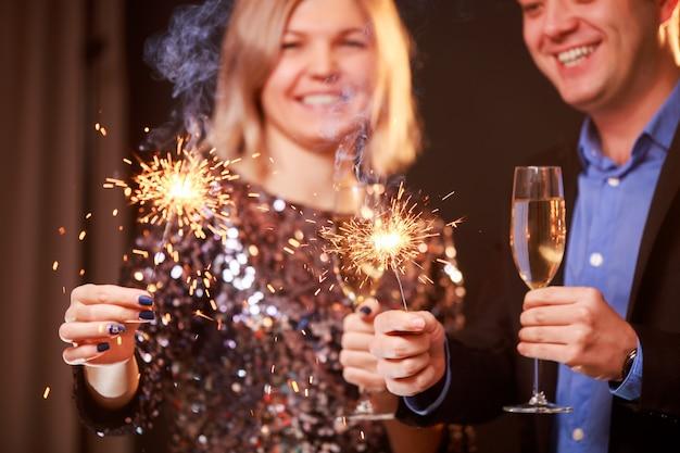 黒の背景にシャンパングラスと線香花火と幸せなカップルの画像