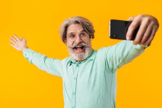 Изображение счастливого эмоционального седого человека, позирующего изолированным на желтой стене, делает селфи по мобильному телефону.