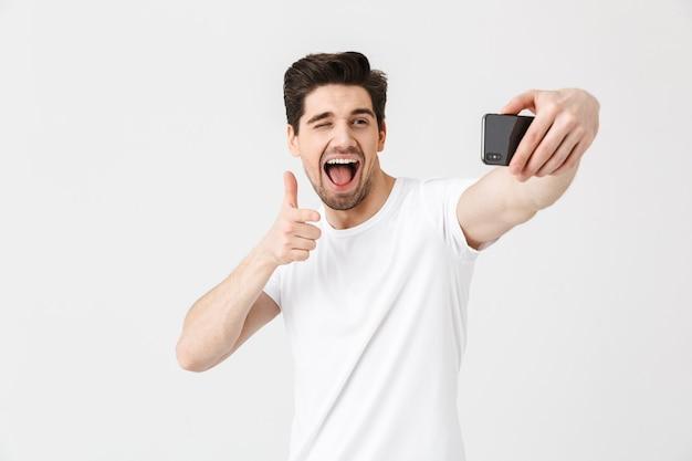 Изображение счастливого эмоционального молодого человека, позирующего изолированно над белой указывая на стену, принимает селфи по мобильному телефону.