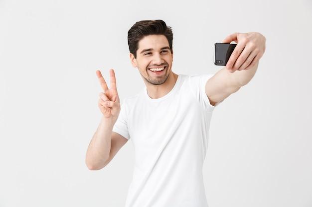 Изображение счастливого эмоционального молодого человека, позирующего изолированным над белой стеной, показывающим жест мира, принимает селфи по мобильному телефону.