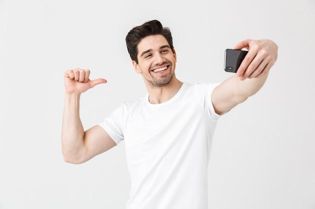 Изображение счастливого эмоционального молодого человека, позирующего изолированным над белой стеной, принимает селфи по мобильному телефону, указывая на себя.