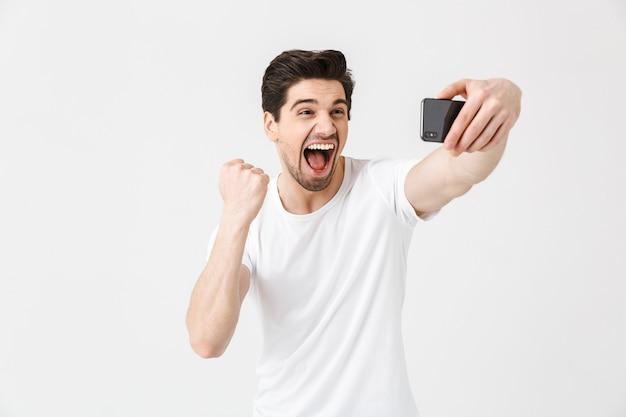 Изображение счастливого эмоционального молодого человека, позирующего изолированно над белой стеной, принимает селфи по мобильному телефону, показывая жест победителя.