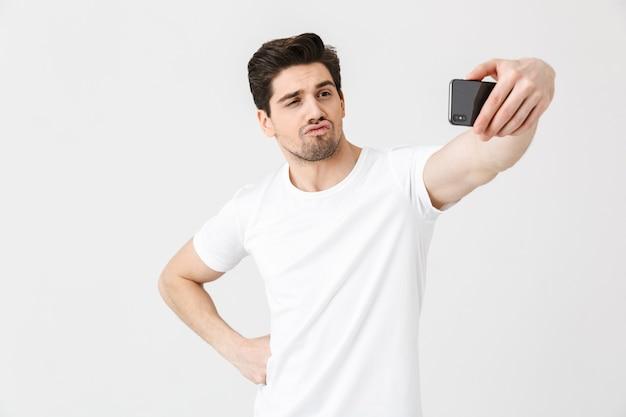 Изображение счастливого эмоционального молодого человека, позирующего изолированным над белой стеной, принимает селфи по мобильному телефону.