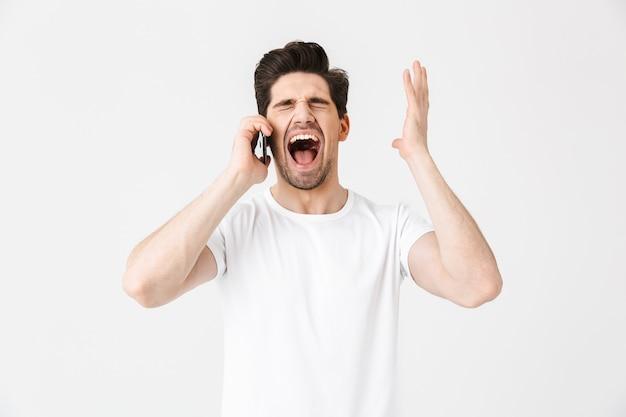 携帯電話で話している白い壁の上に孤立してポーズをとって幸せな興奮ショックを受けた若い男の画像。