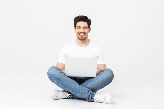Изображение счастливого возбужденного молодого человека позирует изолированным над белой стеной с помощью портативного компьютера.