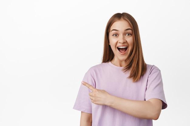 ブロンドの髪、興奮して驚いて笑って、左指を指して、ロゴ、方向またはバナーへの道を示して、白い壁に立って幸せな女性モデルの画像