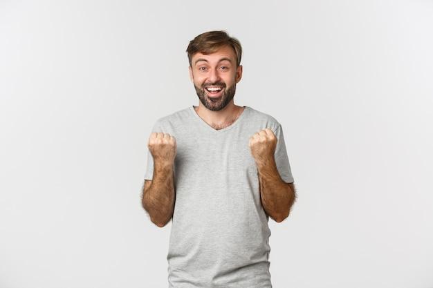 喜んで、拳を握り締めて、はいと言って、目標を達成し、賞を獲得する幸せなハンサムな男の画像