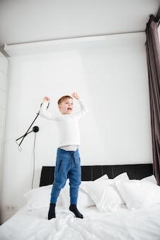 Изображение счастливого маленького мальчика прыгает на кровати у себя дома. посмотри в сторону.