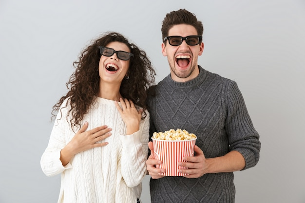 Изображение счастливого мужчины и женщины в 3d-очках, держащих ведро с попкорном, изолированные на серой стене
