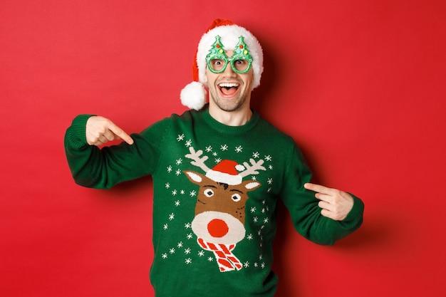 パーティーグラスとサンタ帽子をかぶって、彼のクリスマスセーターを指して、笑顔で、赤い背景の上に立っている幸せな男の画像