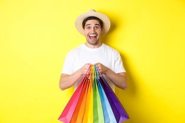 휴가지에서 쇼핑하는 행복한 남자의 이미지, 종이 가방을 들고 웃고, 노란색 배경에 서서