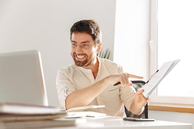 Изображение счастливого офисного работника 30-х годов в белой рубашке с ноутбуком и бумажными документами, сидя за столом на современном рабочем месте