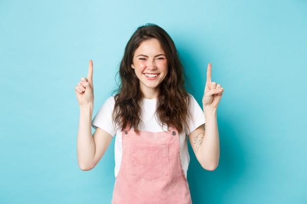 곱슬머리를 한 행복한 미소 짓는 젊은 여성의 이미지, 웃고, 로고 배너를 손가락으로 가리키며, 프로모션 거래를 보여주고, 파란색 배경에 서 있는 이미지.