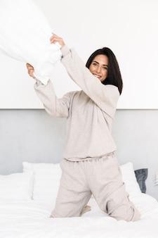 自宅のベッドで枕を楽しみながら笑っている幸せな女性30代の画像
