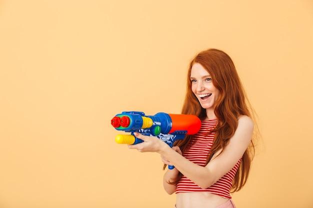 水鉄砲のおもちゃを保持している黄色の壁の上に孤立してポーズをとって幸せな若い美しい赤毛の女性の画像。
